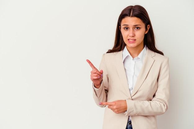Giovane donna d'affari indiana isolata su bianco scioccata indicando con il dito indice uno spazio di copia.