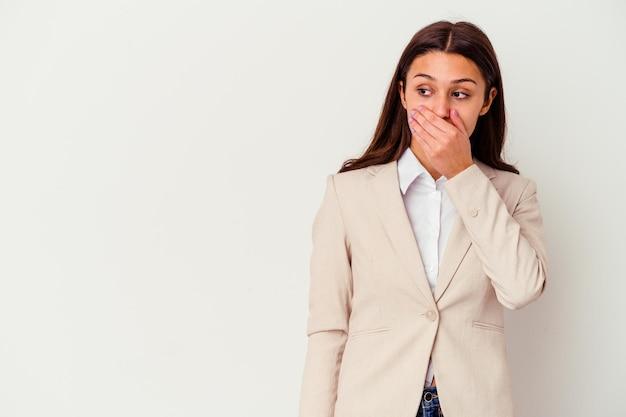 Giovane donna d'affari indiano isolato su bianco premuroso cercando di uno spazio di copia che copre la bocca con la mano.