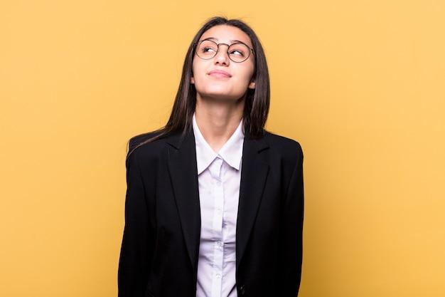 Giovane donna indiana di affari su giallo che sogna di raggiungere obiettivi e scopi