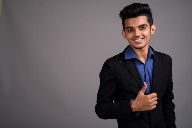 Giovane uomo d'affari indiano contro la parete grigia