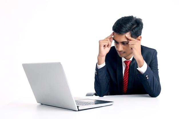 Giovane uomo d'affari indiano o dipendente che si sente triste e stressato in ufficio