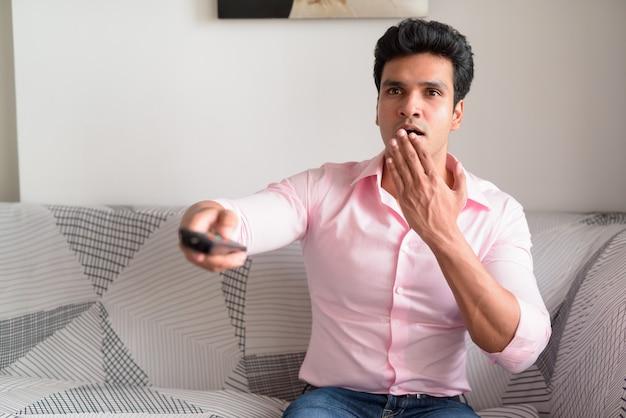 Giovane imprenditore indiano guardando scioccato mentre si guarda la tv a casa