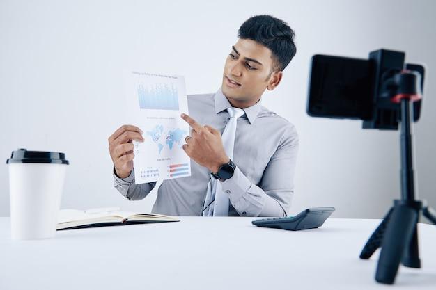 Giovane uomo d'affari indiano che mostra il grafico e spiega i dettagli durante la videoconferenza con i colleghi