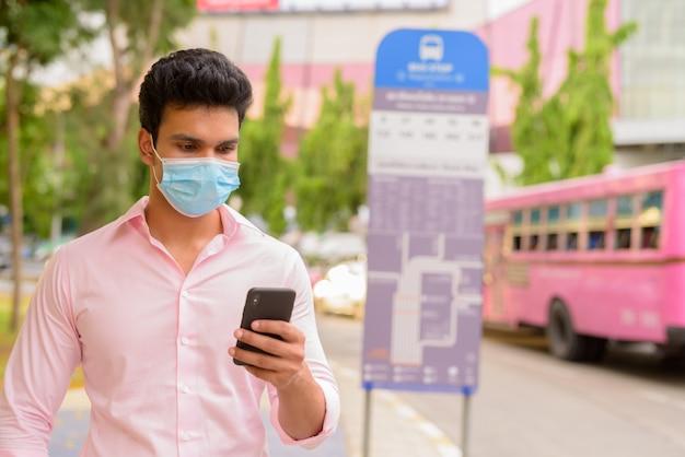 Giovane imprenditore indiano utilizzando il telefono e indossando la maschera alla fermata dell'autobus