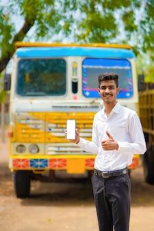 Giovane uomo d'affari indiano con il suo camion o camion e mostrando lo smartphone.