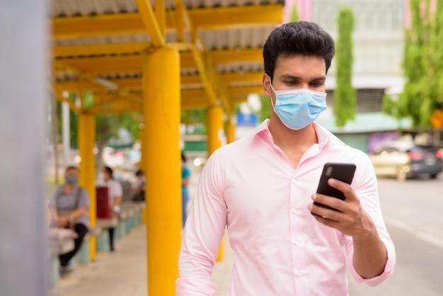 Giovane imprenditore indiano con maschera utilizzando il telefono alla fermata dell'autobus