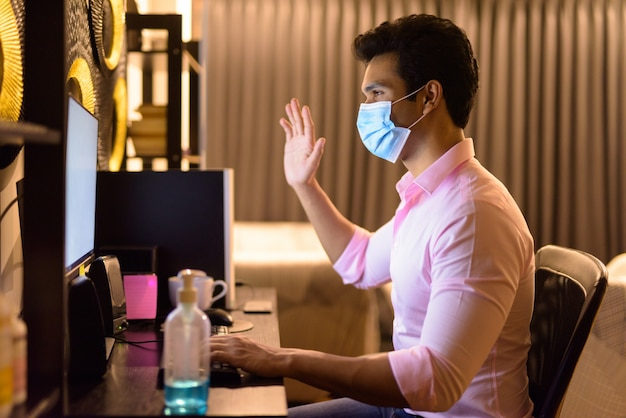 Giovane uomo d'affari indiano con videochiamata maschera durante il lavoro straordinario a casa durante la quarantena