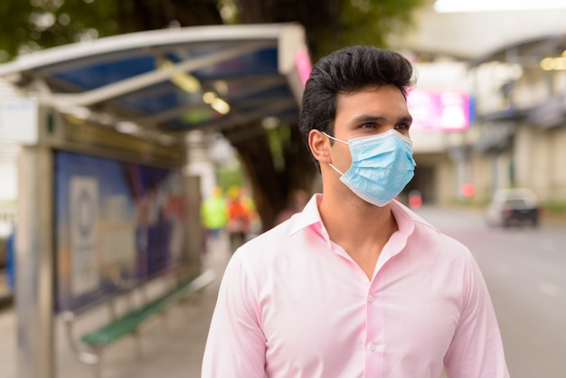 Giovane imprenditore indiano con maschera in attesa alla fermata dell'autobus