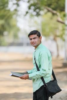 Giovane studente di college indiano o cerca lavoro che tiene file in mano.
