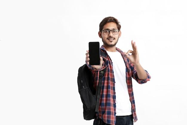 Giovane studente di college indiano che mostra lo schermo dello smartphone sul muro bianco