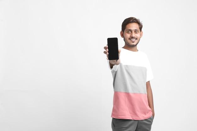 Giovane studente di college indiano che mostra lo schermo dello smartphone