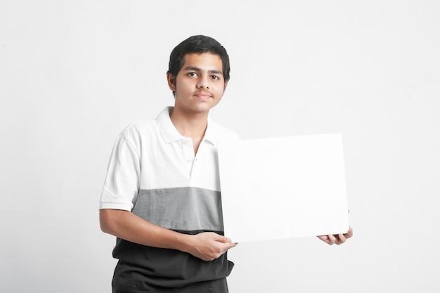Giovane studente di college indiano che mostra bordo bianco sulla parete bianca