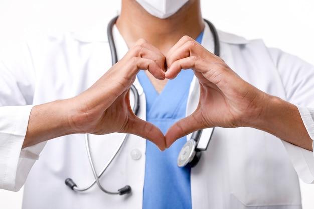 Il giovane medico indiano che fa la forma del cuore con consegna su fondo bianco.