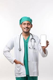 Giovane medico indiano che mostra lo schermo dello smartphone su sfondo bianco.