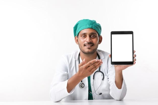 Giovane medico indiano che mostra lo schermo del tablet in clinica.