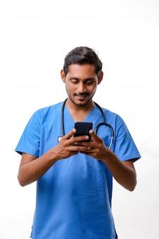 Giovane medico indiano che utilizza smartphone su sfondo bianco.