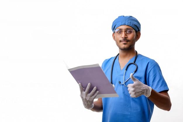 Giovane medico indiano con un blocco note stetoscopio e mostrando i pollici su sfondo bianco.
