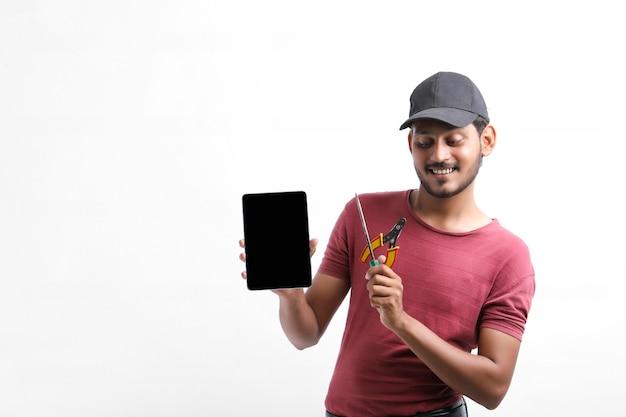 Giovane elettricista indiano che tiene in mano gli strumenti e mostra lo smartphone.