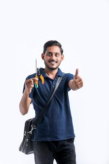 Giovane elettricista indiano che tiene in mano gli strumenti e controlla lo sfondo bianco.