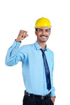 Giovane ingegnere indiano che indossa un elmetto di colore giallo e fa un gesto di successo.
