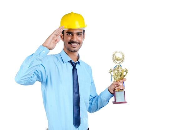 Giovane ingegnere indiano che indossa elmetto di colore giallo con trofeo vincente.