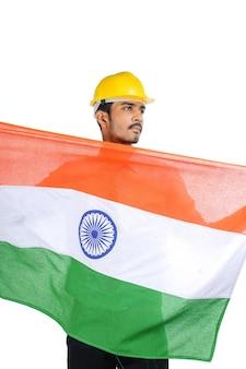 Giovane ingegnere indiano con elmetto di colore giallo e sventolando la bandiera tricolore nazionale.