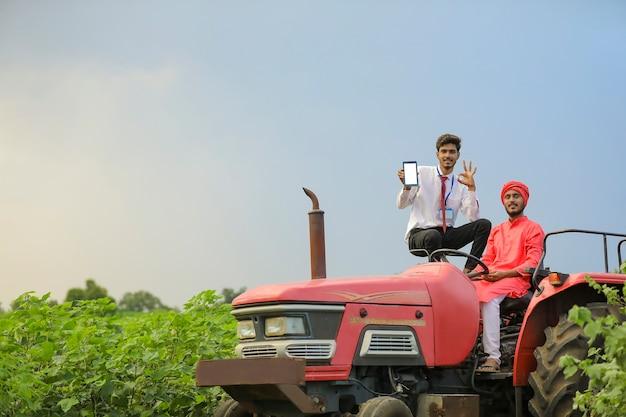 Giovane agricoltore indiano e agronomo seduto sul trattore e mostrando lo schermo dello smartphone