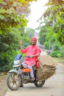 Il giovane agricoltore indiano raccoglie la borsa della tela di sacco sulla bici del motore