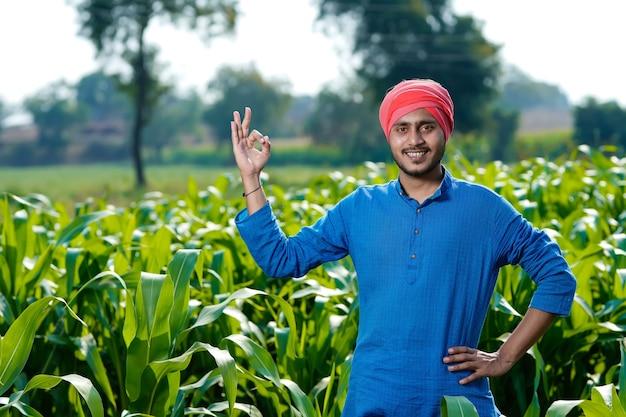 Giovane agricoltore indiano al campo di mais