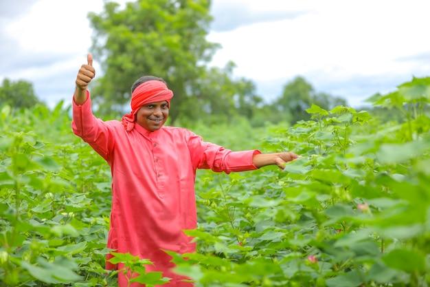 Giovane agricoltore indiano al campo di cotone