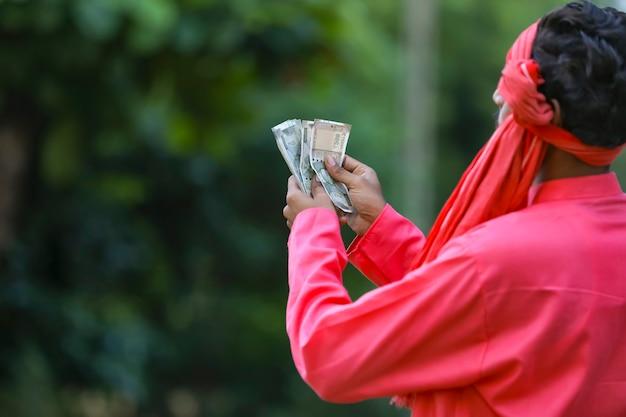 Giovane agricoltore indiano che conta soldi