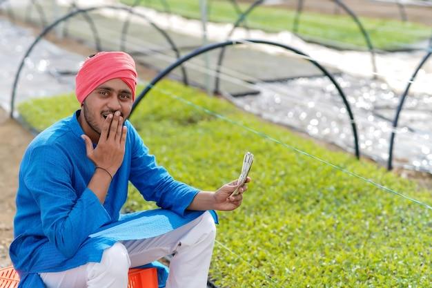 Giovane agricoltore indiano che conta e che mostra i soldi alla serra