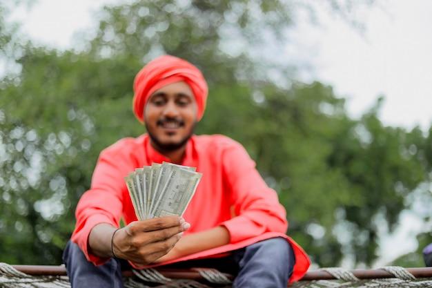 Giovane agricoltore indiano che conta e che mostra i soldi