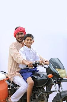 Giovane agricoltore indiano che lascia cadere il figlio a scuola in bicicletta.
