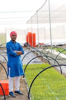 Giovane agricoltore indiano in serra o poli casa