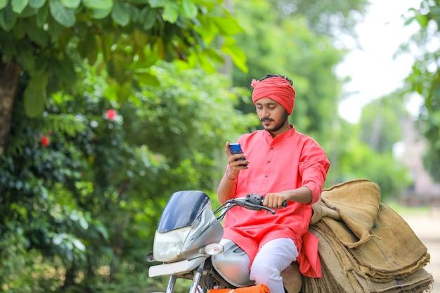 Giovane agricoltore indiano sulla moto e utilizzando smart phone