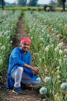 Giovane agricoltore indiano al campo di agricoltura della cipolla