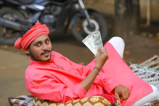 Giovane agricoltore indiano in posa con i soldi