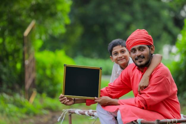 Giovane agricoltore indiano che mostra lavagna in bianco con suo figlio
