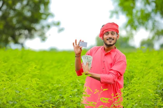 Giovane agricoltore indiano che mostra carta al campo verde
