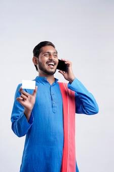 Giovane agricoltore indiano che mostra la carta e parla al telefono cellulare su sfondo bianco