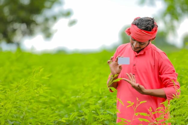 Giovane agricoltore indiano che mostra una carta di credito