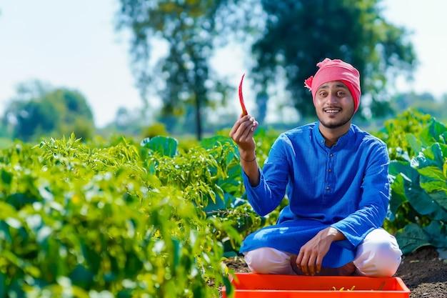Giovane agricoltore indiano che mostra freddo rosso al campo agricolo