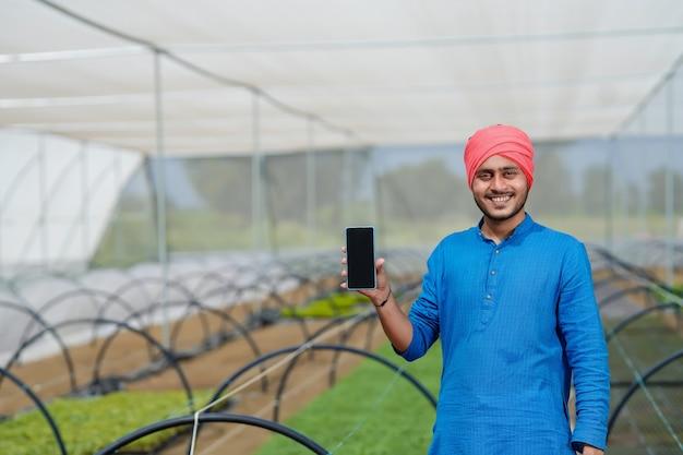 Giovane agricoltore indiano che mostra smartphone in poli casa o serra