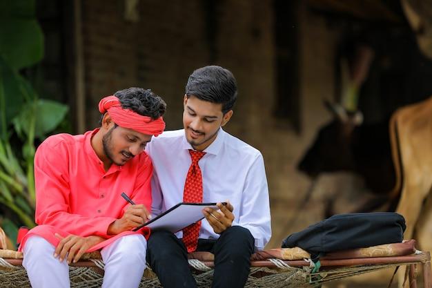 Giovane agricoltore indiano che firma un documento con il banchiere a casa