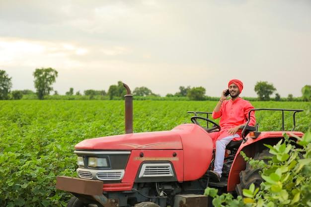 Giovane agricoltore indiano seduto sul trattore e parlando su smartphone al campo