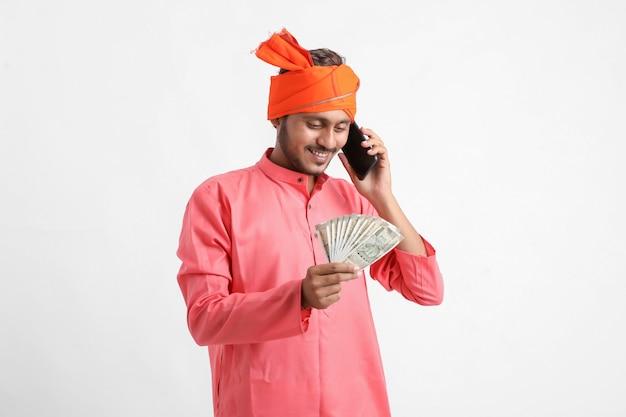 Giovane agricoltore indiano parlando al telefono cellulare e mostrando denaro su sfondo bianco.