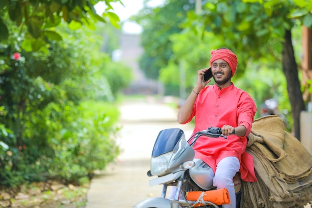 Giovane agricoltore indiano parlando al telefono cellulare