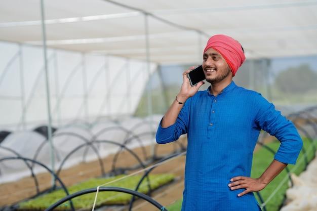 Giovane agricoltore indiano parlando al telefono intelligente in serra