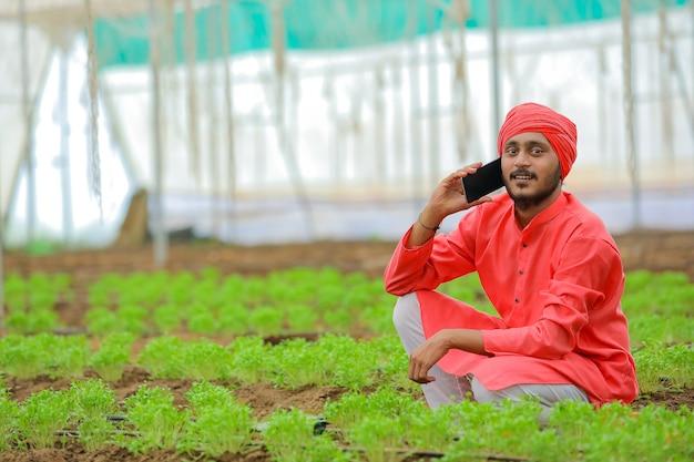 Giovane agricoltore indiano parlando su smartphone in poli casa
